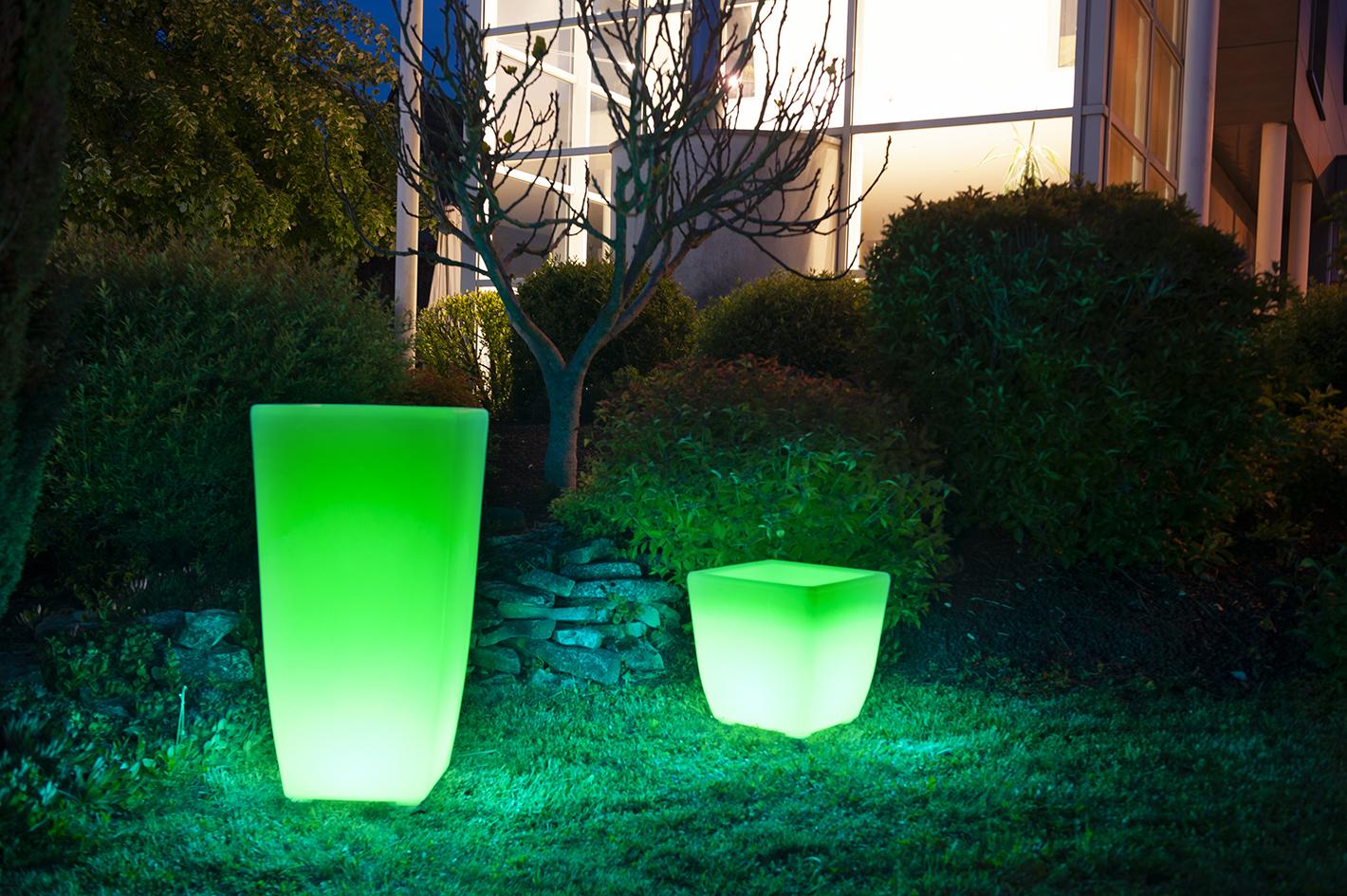Un vase et pot lumineux à Led vert au bord d'une piscine